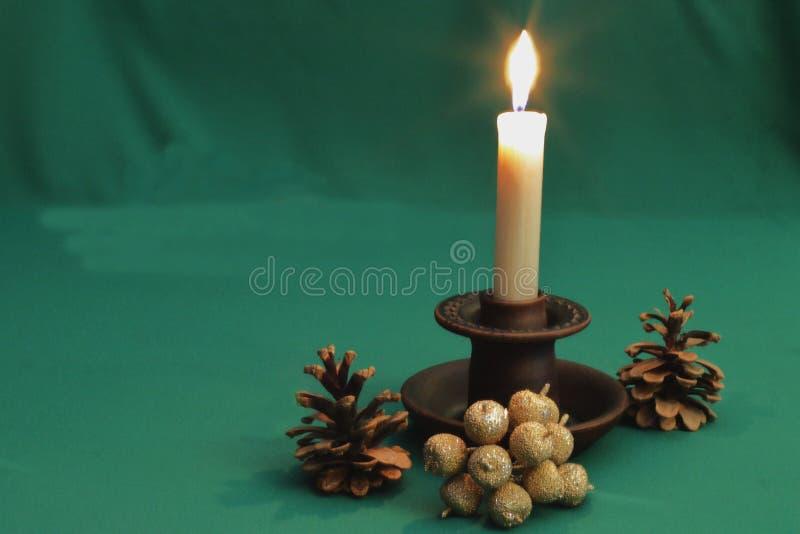 Den härliga leraljusstaken med bränningstearinljuset, sörjer kottar och en dekorativ bukett av guld- äpplen på grön bakgrund arkivfoto