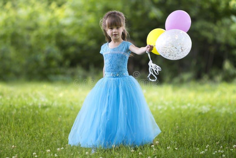 Den härliga lilla blonda långhåriga flickan i den trevliga långa blåa aftonklänningen som ser som prinsessa, ser in camera rymma  arkivfoton