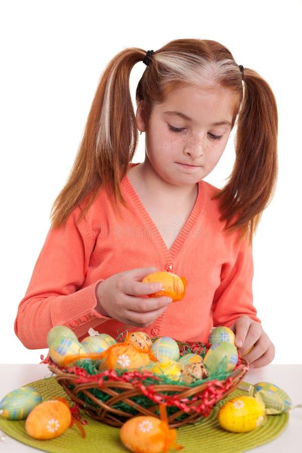Den härliga lilla flickan dekorerar korgen med påskägg arkivbild