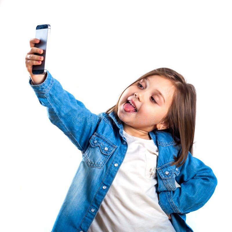 Den härliga lilla flickan gör selfie genom att använda en smart telefon, på vit bakgrund royaltyfri foto