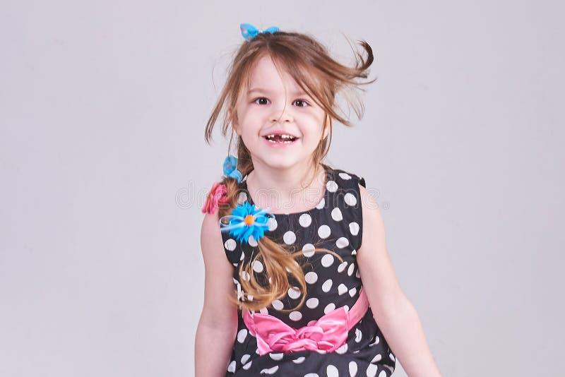 Den härliga lilla flickan hoppar och ler arkivbilder