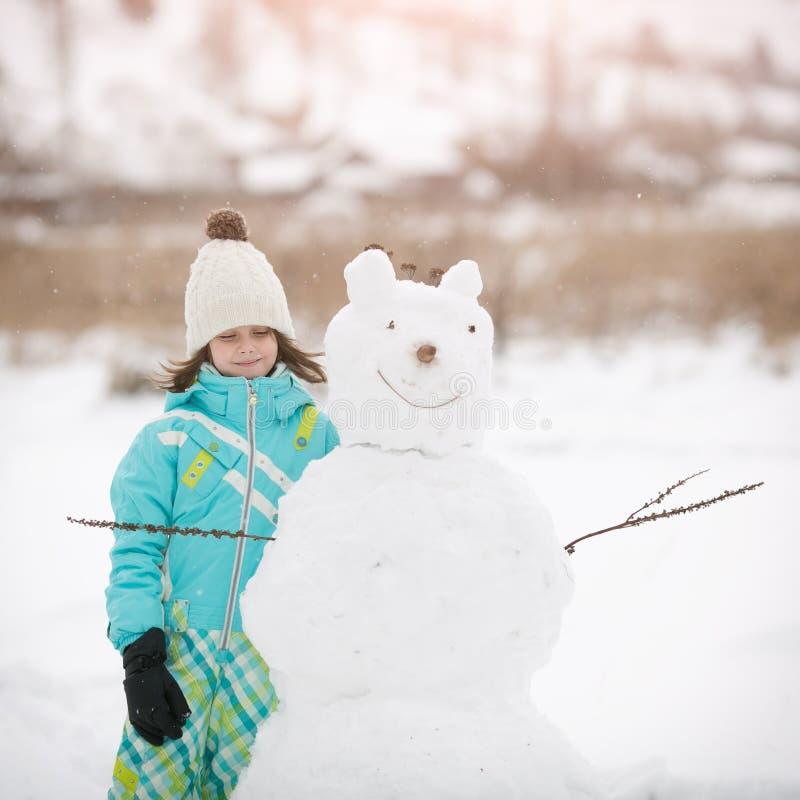 Den härliga lilla flickan hugger snögubben arkivbild