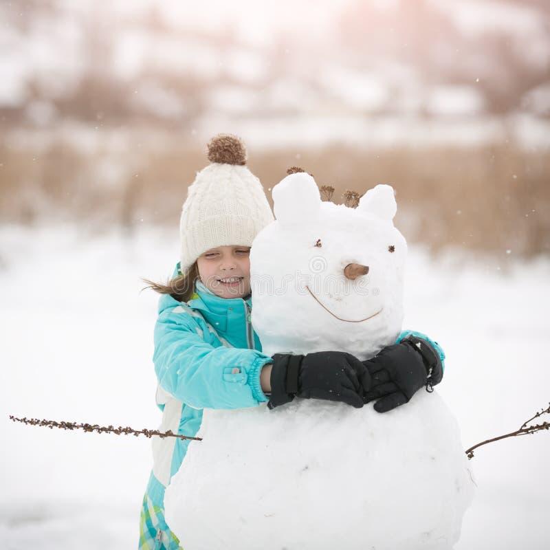 Den härliga lilla flickan hugger snögubben royaltyfri foto