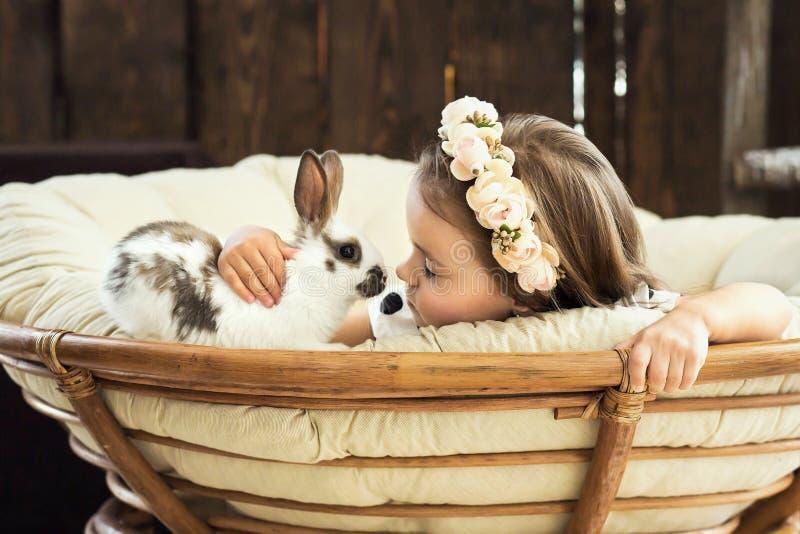 Den härliga lilla flickan i en krans av blommor kysser en gullig fluffig vit påskkanin royaltyfri foto