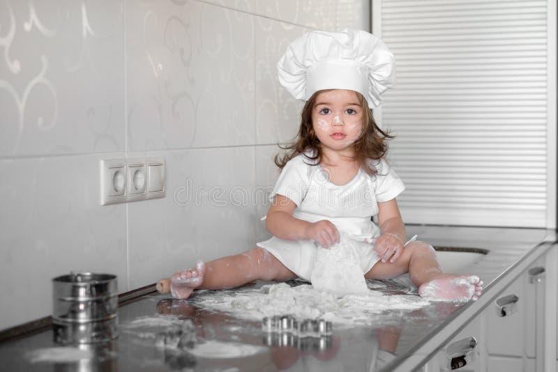 Den härliga lilla flickan lär att laga mat ett mål i köket arkivfoton