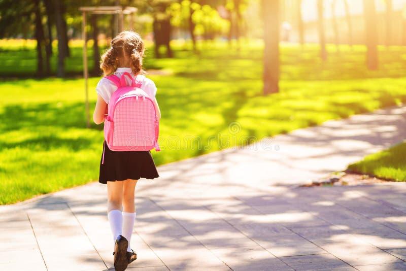 Den härliga lilla flickan med ryggsäcken som går i, parkerar klar baksida till skola, tillbaka sikten, nedgångdet fria, utbildnin arkivbild