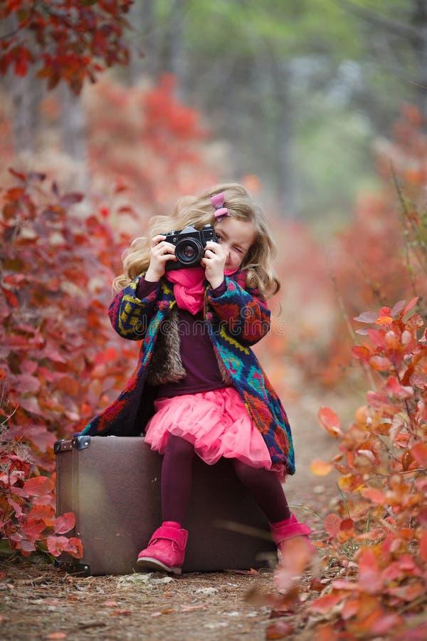 Den härliga lilla flickan reser med en gammal resväska och en kamera i höstskogen arkivfoton