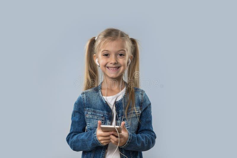 Den härliga lilla flickan som använder den cellSmart telefonen, lyssnar lyckligt isolerat le för musikkläderhörlurar arkivfoto