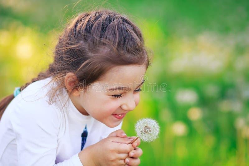 Den härliga lilla flickan som blåser maskrosblomman och ler i sommar, parkerar Lycklig gullig unge som har roligt utomhus arkivbild