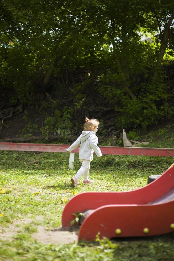 Den härliga lilla flickan som kör runt om lekplatsen från hennes moder på i barn, parkerar under den angenäma solen royaltyfri fotografi