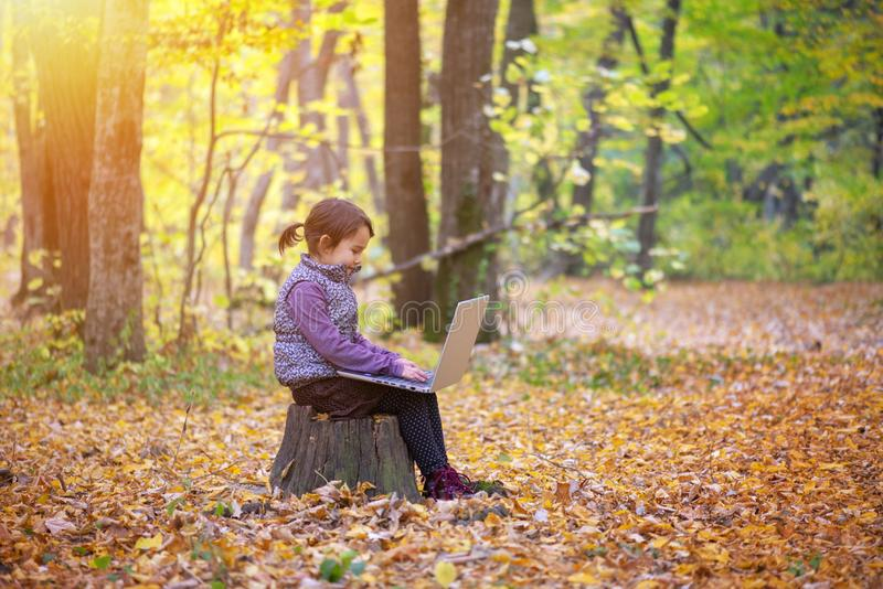 Den härliga lilla flickan står på en stam av att le för träd royaltyfri fotografi