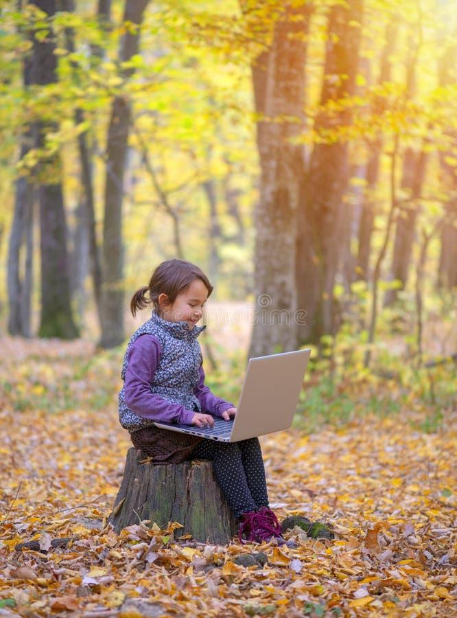 Den härliga lilla flickan står på en stam av att le för träd royaltyfria foton