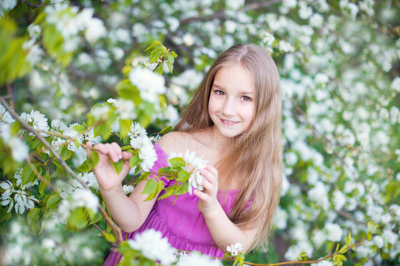 Den härliga litet barnflickan i rosa färgklänning i blomning blommar royaltyfria foton