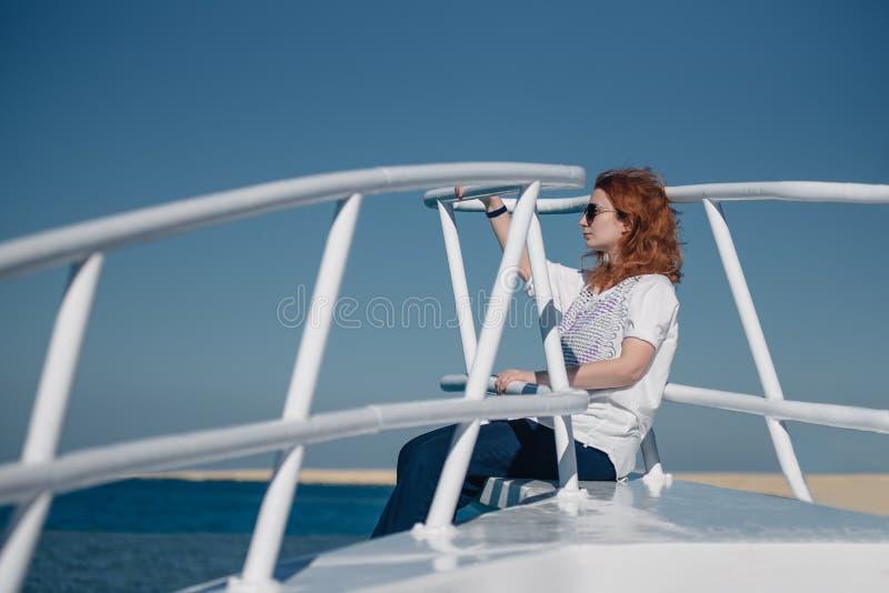 Den härliga ljust rödbrun kvinnan i solexponeringsglas sitter på en vit yacht i ett hav med klart turkosvatten Avkoppling på somm royaltyfria foton