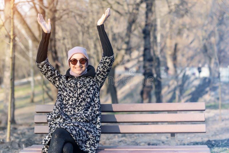 Den härliga lyckliga caucasian kvinnan i omslag, hatten och solglasögon tycker om att sitta på bänk på staden parkerar eller skog arkivbilder