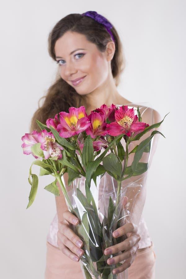 Den härliga lyckliga flickan ger en lös orkidé royaltyfri bild