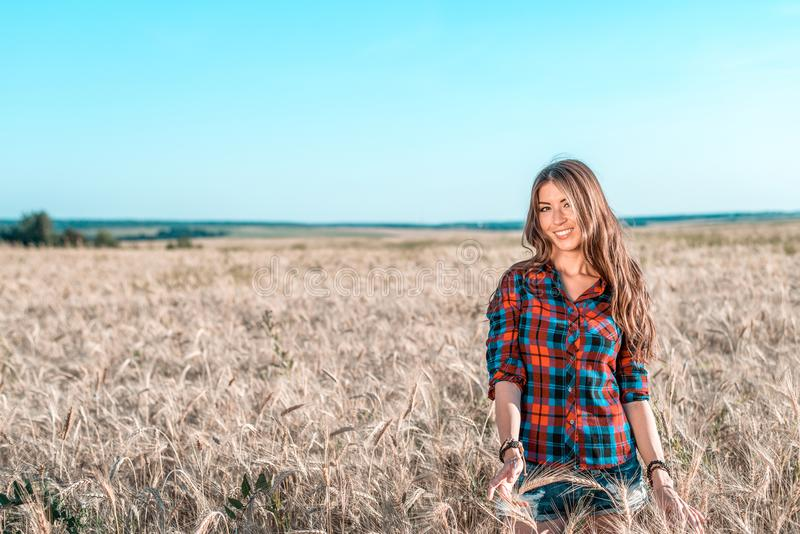 Den härliga lyckliga flickan i fältet, solig eftermiddag, kortsluter skjortan Begreppet av att tycka om naturen Vila på luften royaltyfri foto