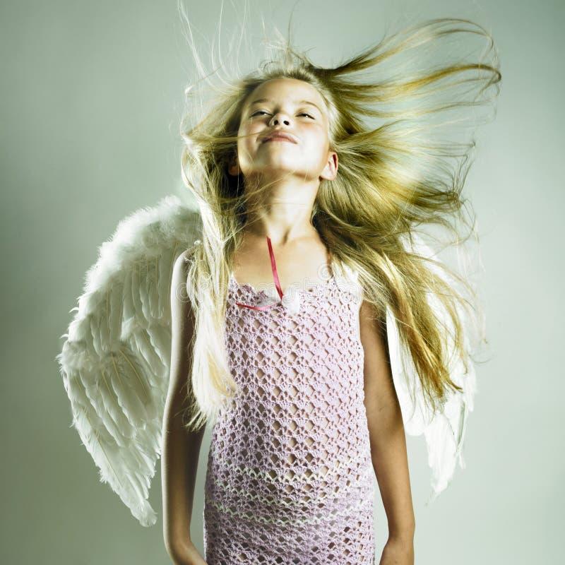 Den härliga lyckliga flickan med ängel påskyndar arkivbilder
