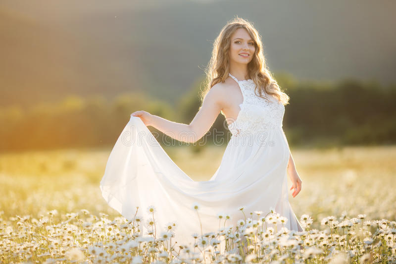 Den härliga lyckliga gravida flickan på fältet av tusenskönan blommar, solnedgångtid royaltyfri bild