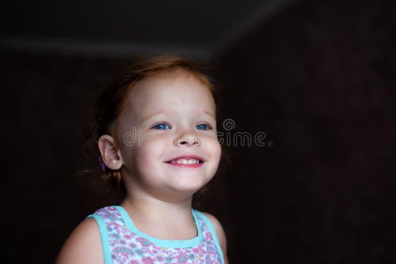 Den härliga lyckliga gulliga lilla rödhårig manflickan ler uppriktigt och skrattar med ett mjukt ljus från fönsterlivsstilen fotografering för bildbyråer