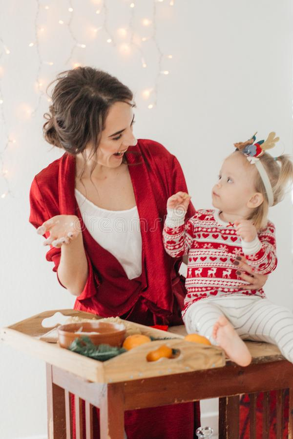 Den härliga lyckliga kvinnan med behandla som ett barn flickan nära en julgran med gåvor fotografering för bildbyråer