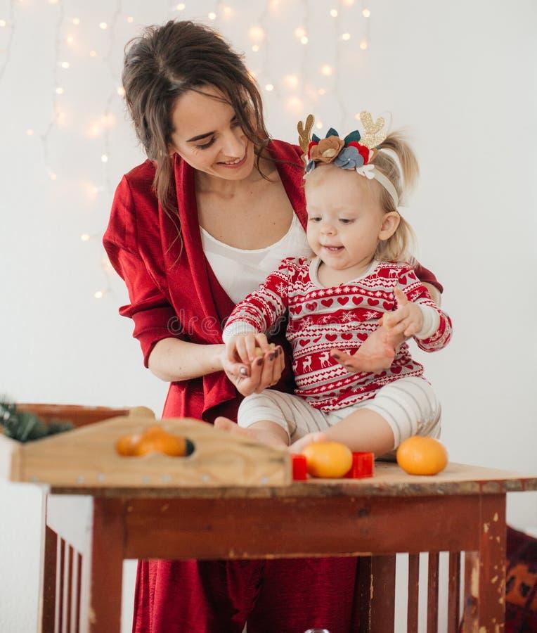 Den härliga lyckliga kvinnan med behandla som ett barn flickan nära en julgran med gåvor arkivfoto