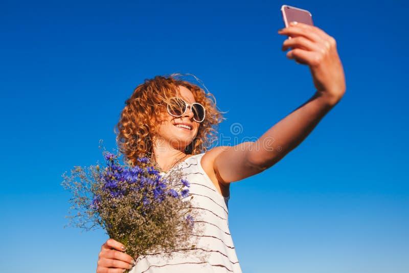 Den härliga lyckliga kvinnan med det röda innehavet för lockigt hår blommar och ta selfie mot blå himmel lycklig din feriesommar  royaltyfri foto
