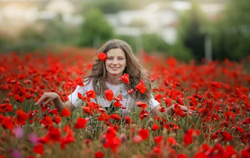Den härliga lyckliga le tonåriga flickaståenden med röda blommor på huvudet som tycker om i vallmo, sätter in naturbakgrund makeu arkivfoton