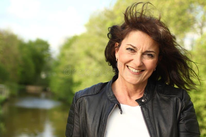 Den härliga lyckliga mogna caucasian kvinnan utanför i parkerar royaltyfri foto
