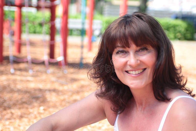 Den härliga lyckliga mogna caucasian kvinnan utanför i parkerar royaltyfri fotografi