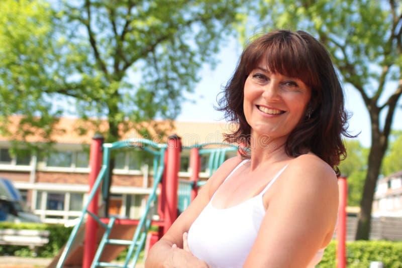 Den härliga lyckliga mogna caucasian kvinnan utanför i parkerar royaltyfria bilder