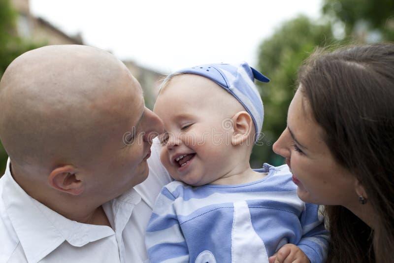 Den härliga lyckliga unga familjen med behandla som ett barn royaltyfri fotografi