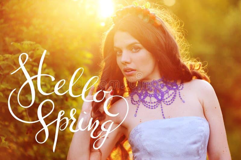 Den härliga lyckliga unga kvinnan som tycker om lukten i en blomningvårträdgård med bokstäver Hello, sprintar arkivbilder
