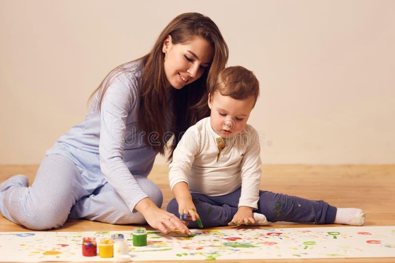 Den härliga lyckliga unga modern och hennes iklädda hem- kläder för liten son sitter på trägolvet i rummet och royaltyfri fotografi