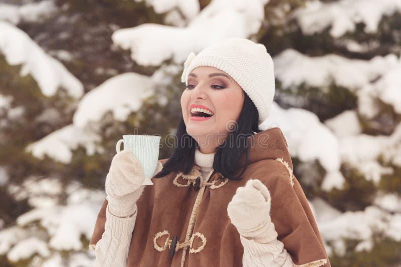Den härliga lyckliga vinterkvinnan med rånar utomhus- royaltyfri bild