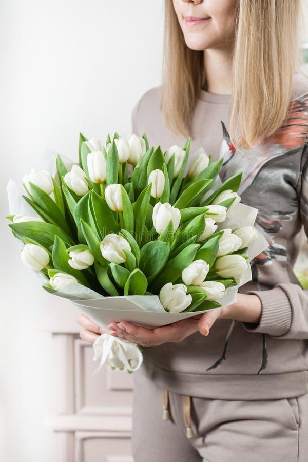 Den härliga lyxiga buketten av vita tulpan blommar i kvinnahand arbetet av blomsterhandlaren på en blomsterhandel gulligt älskvär arkivfoto