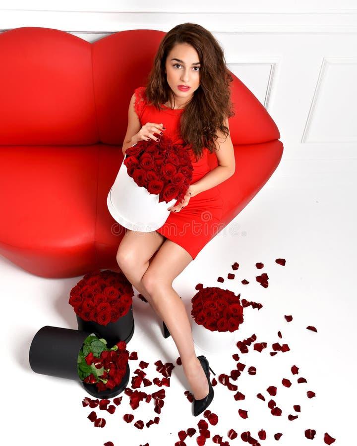 Den härliga lyxiga trendiga kvinnan lägger benen på ryggen i höga kullar och röd dr royaltyfri fotografi