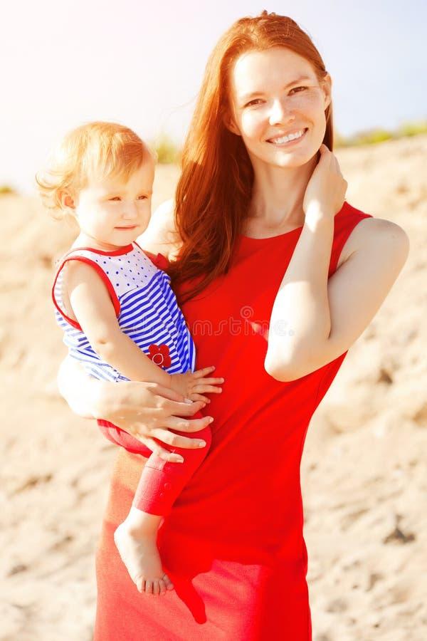 Den härliga mamman och behandla som ett barn utomhus Lycklig familj som spelar på beaen arkivfoto