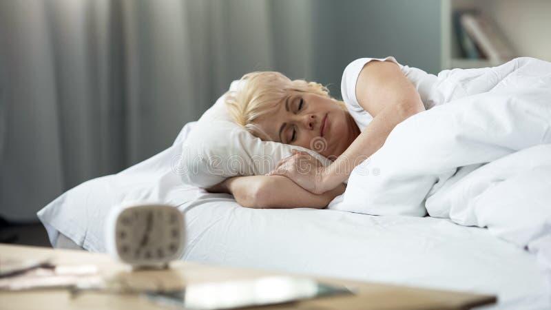Den härliga medelåldersa damen som sover i säng, sömncirkuleringen som är fridsam vilar, vård- arkivbild