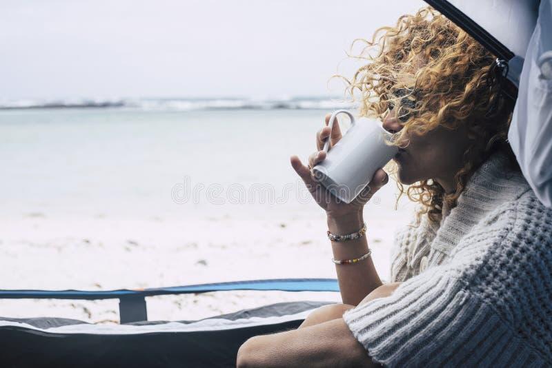 Den h?rliga mellersta ?lderkvinnan sitter ner inom ett t?lt i campa utomhus- k?nsla f?r fri strand naturstunddrinken ett te eller royaltyfri fotografi