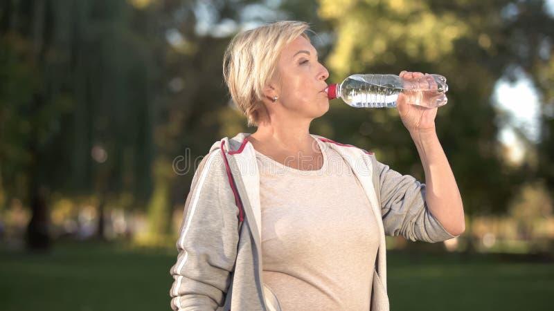Den härliga mitt åldrades kvinnadricksvatten, når den har avslutat hennes morgongenomkörare royaltyfria bilder