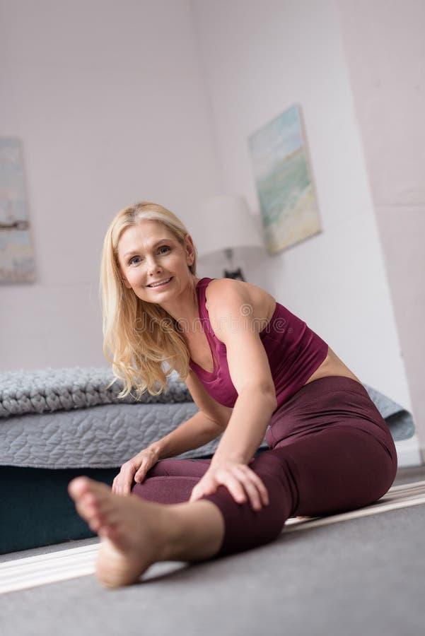 den härliga mitt åldrades kvinnan som övar på matt yoga och ler på kameran arkivfoton