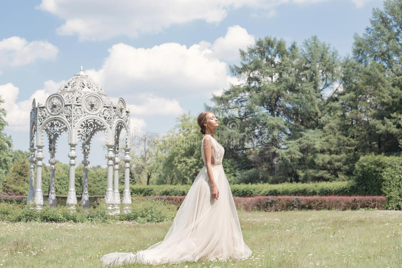 Den härliga mjuka bruden för den unga kvinnan i hennes försiktiga luft för bröllopsklänningen går i den frodiga trädgården på en  royaltyfri fotografi