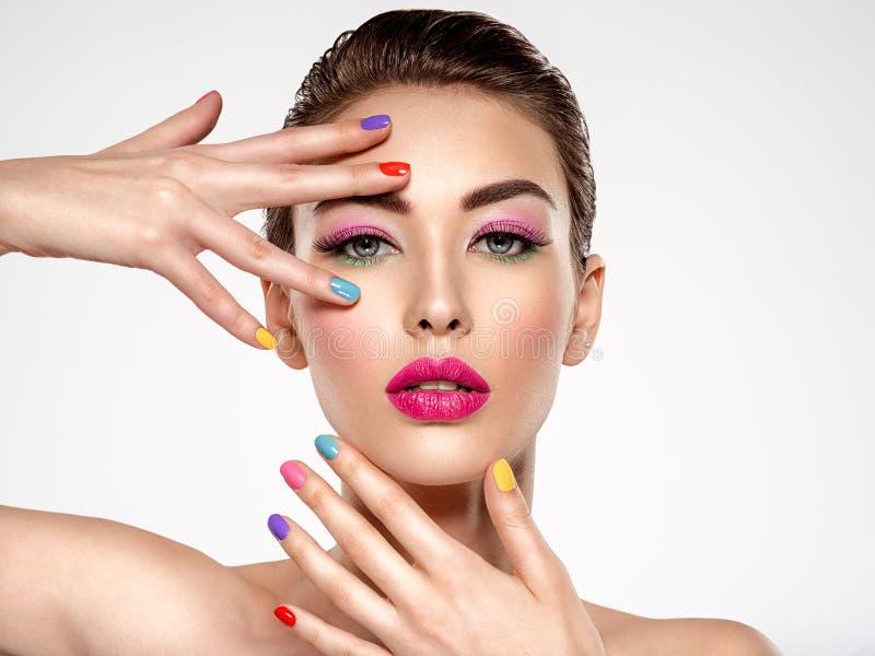 Den härliga modekvinnan med färgad spikar Attraktiv vit flicka med flerfärgad manikyr arkivbild