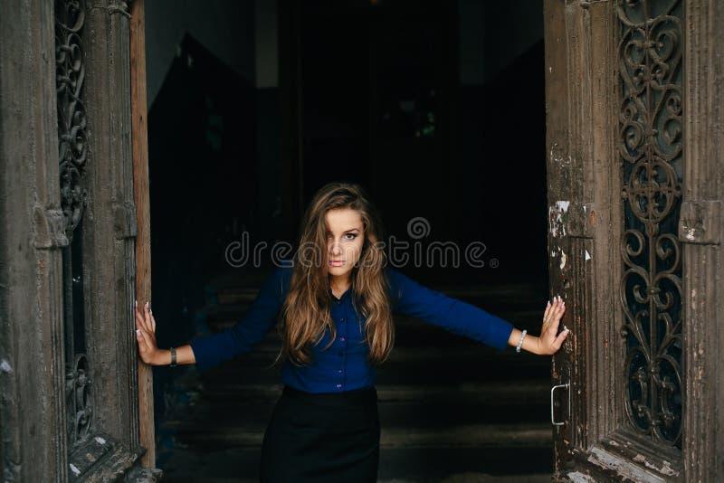 Den härliga modellen öppnar en gammal dörr royaltyfri foto