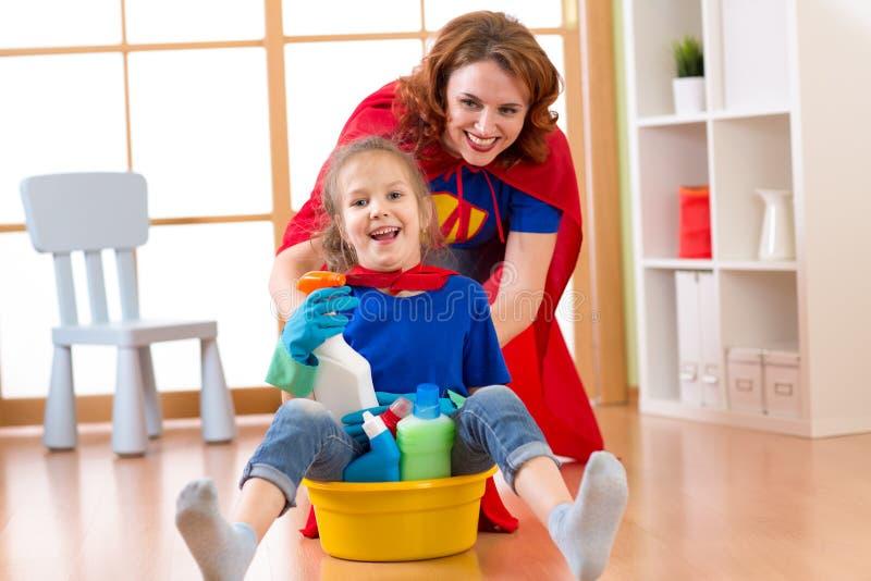 Den härliga modern och hennes gulliga lilla dotter klädde som superheroes som gör ren och spelar royaltyfri fotografi