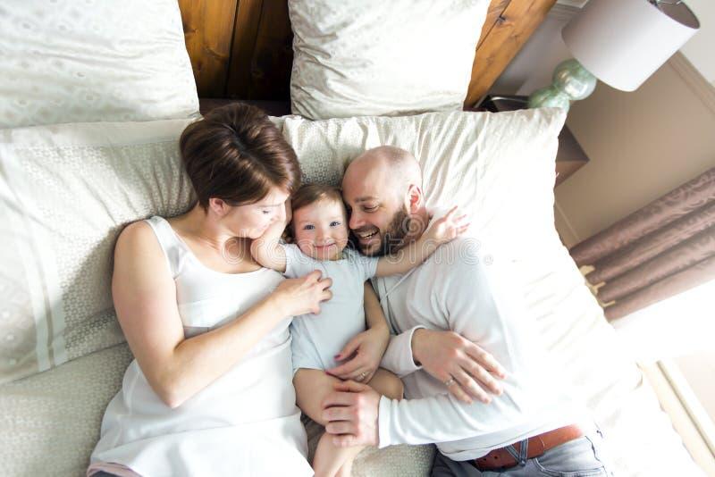 Den härliga modern och den stiliga fadern med behandla som ett barn dottern som ligger på sovrum arkivbilder