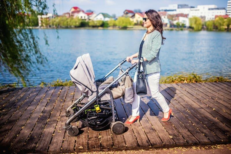den härliga modern som går lilla barnet i stads-, parkerar med nytt behandla som ett barn sittvagnen royaltyfri fotografi