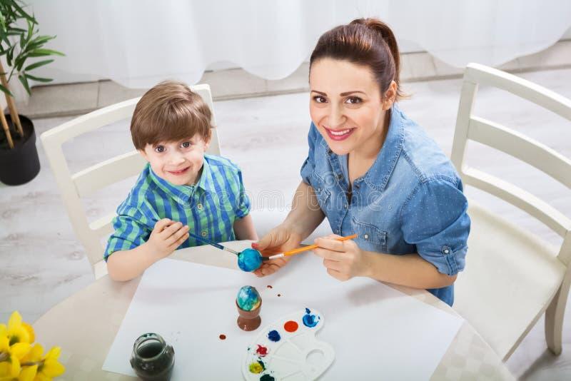 Den härliga modern undervisar sonen hur man målar easter ägg royaltyfria bilder