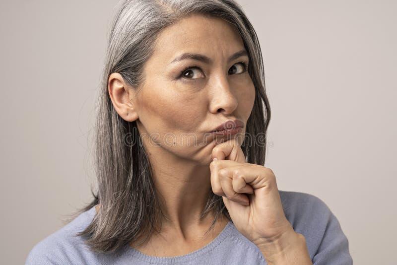 Den härliga mogna kvinnan blåser kanter, medan trycka på hennes haka arkivfoton